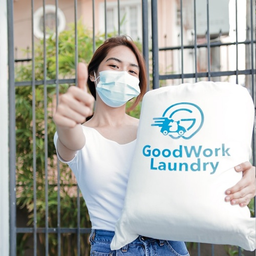 Woman wearing facemask, holding bag of laundry, giving a thumbs up